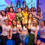 Gruppenfoto der Teilnehmerinnnen vor einem großen Bildschirm mit dem BayFiD Logo - in der Mitte sitzen Dorothee Bär, Judith Gerlach und Tijen Onaran