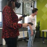 Eine Frau trägt eine Virtual Reality Brille und hält Steuerungsgeräte in den Händen.