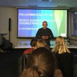 Mann hält Vortrag vor einer kleinen Gruppe. Im Hintergrund ist eine Präsentation mit dem Hinweis auf Bosch Sicherheitssysteme zu sehen.