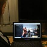 Eine junge Frau betrachtet den Bildschirm eines aufgeklappten Laptops.
