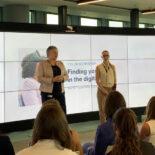 Zwei Frauen halten einen Vortrag vor eine Gruppe - hinter ihnen ein riesiger Bildschirm mit einer Präsentation.