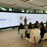 Eine Frau hält einen Vortrag vor eine Gruppe - im Hintergrund eine riesiger Bildschirm mit einer Präsentation.