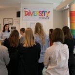 """eine Frau erzählt vor einer kleinen Gruppe junger Frauen. Im Hintergrund hängt ein Banner mit der bunten Aufschrift """"Diversity Corner"""""""