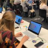 eine Gruppe junger Frauen in einem Schulungsraum sitzt vor ihren Laptops und lauschen einem Vortrag.