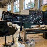 Im Vordergrund befindet sich eine Roboterarm vor einer Autotür - im Hintergrund eine kleine Wand mit verschiedenen Werkzeugen.
