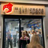 """Eine kleine Gruppe Frauen betritt eine Raum durch eine Glastür. Über der Tür steht der Name """"makerspace"""""""