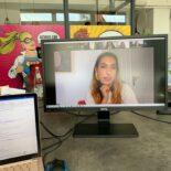 Ein Monitor steht auf dem Boden, daneben ein Laptop. Auf dem Monitor ist Tijen Onaran im Gespräch zu sehen.